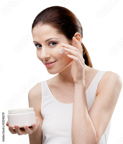 Woman putting on cream from container on face, isolated