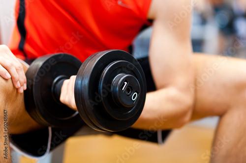 Young athlete lifting weights in the gym