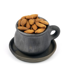 Cup of almonds isolated on white.