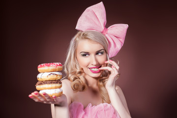 Donuts. Funny woman eating donuts smiling in studio