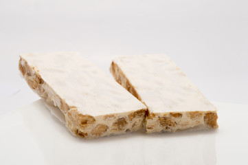 Pieces of Christmas hard almond turron on white plate