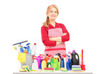 Smiling woman posing with cleaning supplies on a table