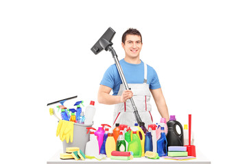 Male cleaner holding a hover and posing with cleaning supplies