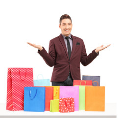 Satisfied young man posing with plenty of shopping bags on a tab