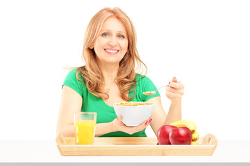 Smiling woman eating cereals and fruit for breakfast