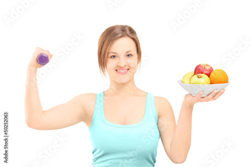 Beautiful young female posing with a dumbbell and fruits in a bo