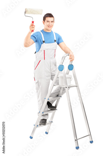 Full length portrait of a male painter holding a roller and stan
