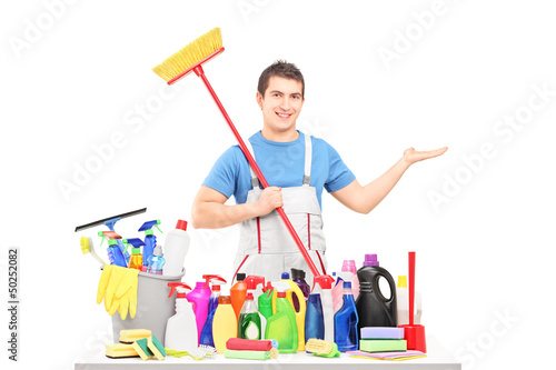 Man in a uniform holding a broom and posing with cleaning suppli