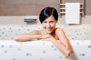 Beautiful attractive girl relaxes in bath, hygiene concept
