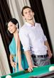 Couple standing near billiard table