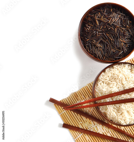 Bowls of uncooked white and wild rice on white background