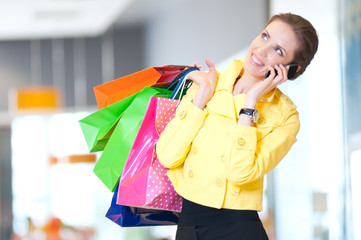 Shopping woman with phone and color bags