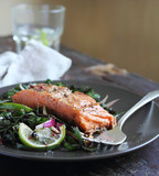 Portion of roasted salmon steak with fresh spring salad