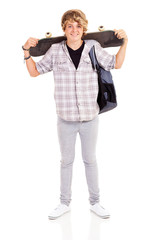 happy teen boy carrying skateboard on his shoulder isolated