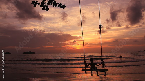 The boy on a swing. The sunset as a background.