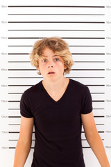 shocked teen boy taking police mug shot