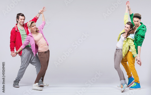 Two hip-hop couples dance and smile
