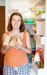woman  with cheese near fridge