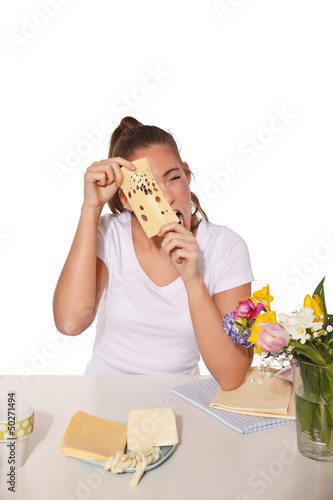 Young woman peeping through a cheese