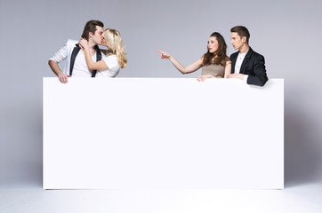 Surprised friends staring at kissing couple