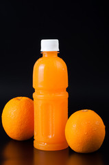 orange juice in a bottle and orange  on black background