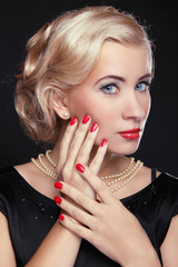 Blond woman with make up and red manicured nails over black, stu