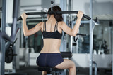 Woman at the gym doing exercises to strengthen muscles of back poster