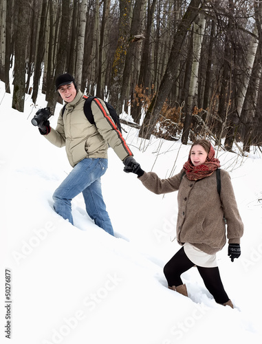 A young couple in the winter forest