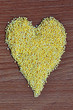 Heart symbol: millet on the wooden background