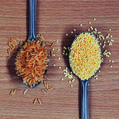 Spoons with brown rice and millet on the wooden background