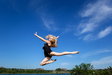 Freedom concept. Dancer jumping against blue sky