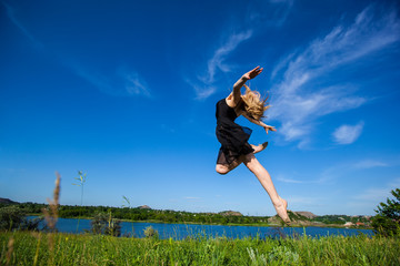 Young  girl doing gymnastic jumps outdoors