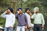 Young indian sikh men with mobile phones