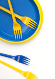Bright blue and yellow plastic disposable tableware on white bac
