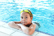 Happy girl with goggles in swimming pool