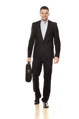 attractive smiling young businessman walking with a laptop bag