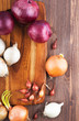 Different varieties of onions on a kitchen board