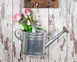 Gießkanne mit Blumenstrauß vor heller, verwitterter Holwand