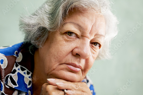 Portrait of serious old woman looking at camera with hands on ch