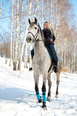 Girl riding on pale horse sunny winter