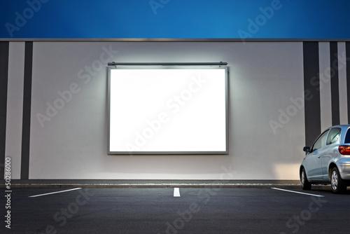 Leinwandbild Motiv Großflächenplakat beleuchtet  an Supermarkt nachts