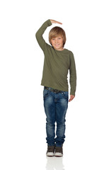 Happy preteen boy pointing measuring what has grown