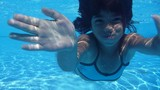 The little girl in the water park swimming underwater