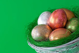 Easter eggs in a basket on a green  background