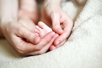 hands holding tiny foot of newborn baby