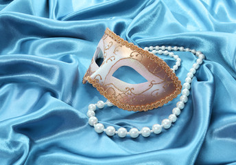 glitter gold mask and pearl necklace on turquoise silk drape