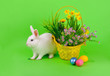 Sweet bunny, colored eggs and flowers on green