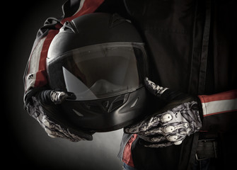 Motorcyclist with helmet in his hands. Dark background