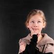 Nachdenkende Schülerin vor schwarzer Tafel