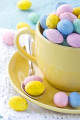 Easter eggs in a yellow cup on wooden background